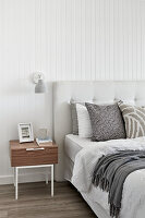 Bed and bedside table in bedroom with white-clad walls