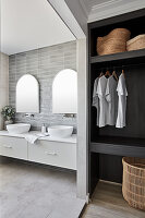 Washstand with twin countertop sinks and walk-in wardrobe in foreground