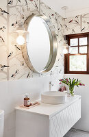 Washstand with round countertop sink below mirror and sconce lamps