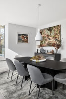 Black dining table with grey upholstered chairs