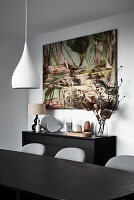 View across dining table to modern artwork on wall above sideboard