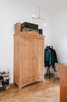 Wooden cupboard in hallway with white walls