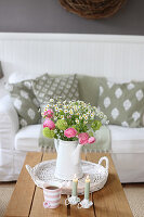 Bouquet of ranunculus, viburnum and feverfew in a coffee pot