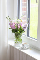 Bouquet of stocks and feverfew on the windowsill