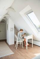 Blonde Frau sitzt am Schreibtisch unter dem Dach