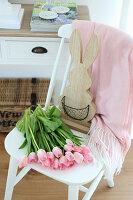 Rosa Tulpen und Holz-Hase auf weißem Stuhl