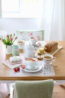 Gedeckter Frühstückstisch mit Müsli, Tee, Kastenbrot und Tulpen
