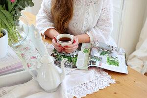Teekane, Zeitschrift und Frauenhand mit Tee