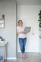 Blonde woman holding laptop