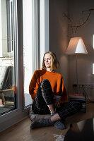 Blonde woman sitting on the floor next to balcony door