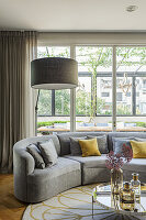 Grey, curved sofa with scatter cushions in front of window