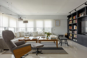 Comfortable armchair with footstool, sofa and tables in front of fitted cabinets with bookshelves and TV
