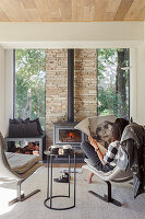 Woman reading the newspaper in front of a fireplace in a bright living room