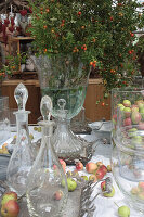 Autumn arrangement with glass carafes, apples and bouquet of rose branches with rose hips