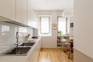 White fitted kitchen, antique wooden table and transparent chairs