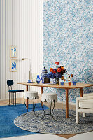 Table with bouquet of flowers and various seating furniture in front of wall with blue and white wallpaper