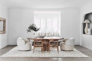 Ovaler Tisch mit Stühlen und bequemen Sesseln vor Fenster mit integrierter Sitzbank