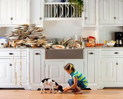 Plates piled high on counter top after a dinner with girl feeding leftovers to dog