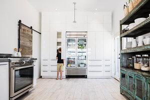 Junge steht vor offenem Küchenschrank