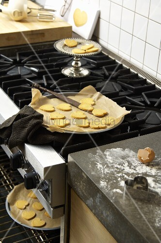 Baked heart biscuits on baking trays in a kitchen