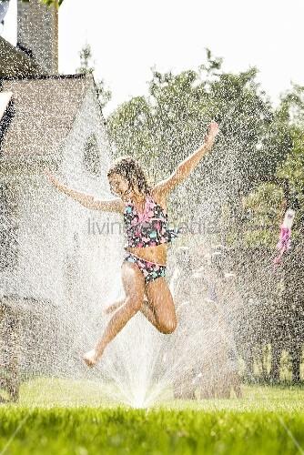 A girl jumping in a sprinkler