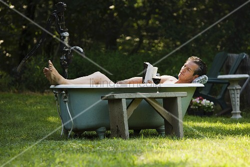 Man in outdoor bathtub