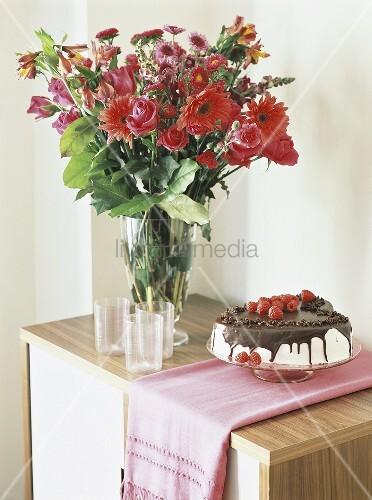 Chocolate cake with cream & raspberries beside vase of flowers