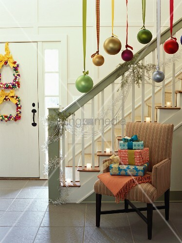 Christmas gifts on chair beside decorated staircase
