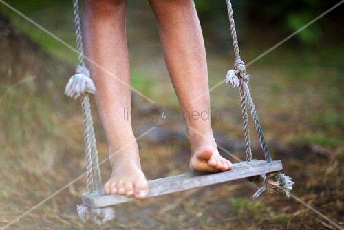 Child standing on swing barefoot