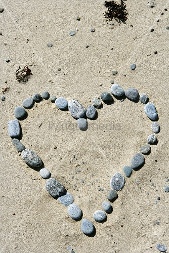 Stones arranged in the shape of a heart in sand