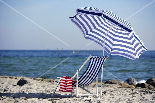 Blue and white deckchair and beach umbrella by the sea
