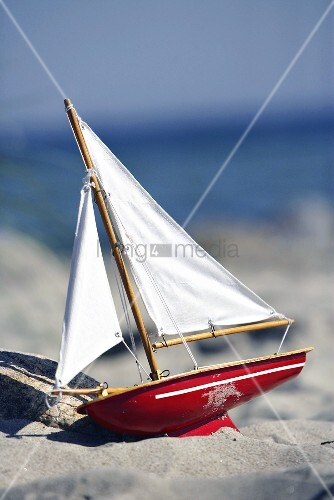 Toy sailing boat on sandy beach