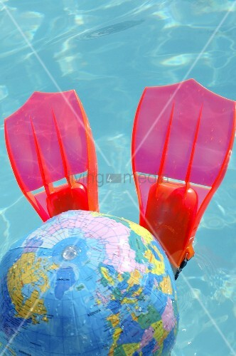 Flippers and globe beach ball in swimming pool