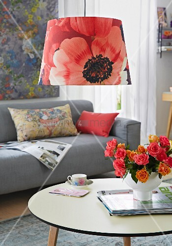 A living room with a sofa, coffee table and a pendant lamp with a poppy shade
