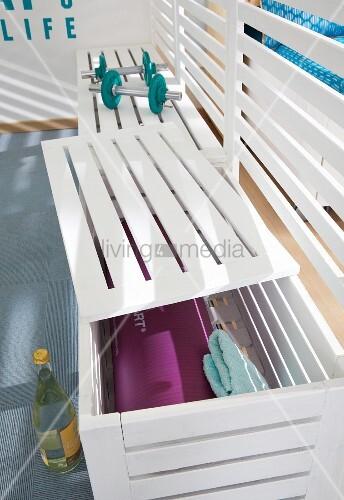 Weiss lackierte Bänke aus Holzlatten als Raumteiler und als Stauraum für Sport-Utensilien