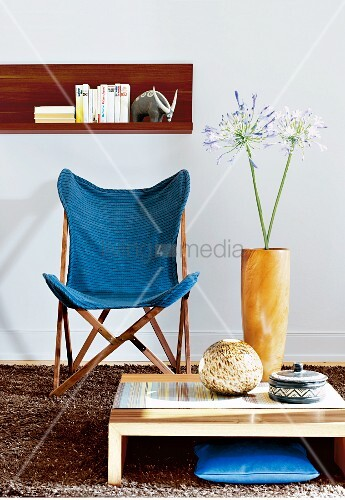An ethnic style living room with a fabric chair and a low coffee table