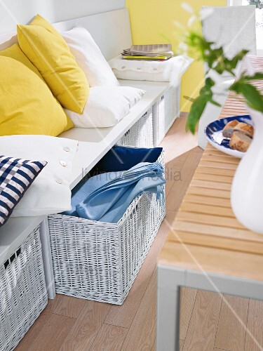 Storage baskets below white bench with scatter cushions