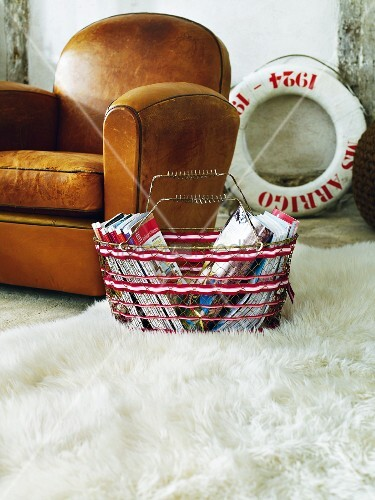 Leather armchair and basket of magazines on white furry carpet
