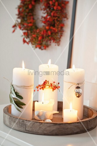 White pillar candles with autumnal decorations on a wooden tray