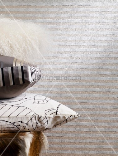 Stack of cushions in front of striped wallpaper