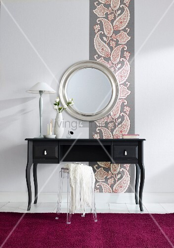 Black dressing table against wallpaper with paisley pattern