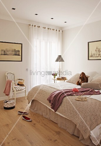 Simple bedroom with double bed and antique chair next to window with closed curtains