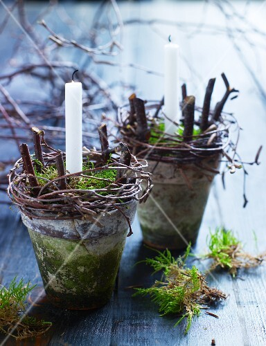 Arrangements of moss, twigs and candles in vintage plant pots on wooden surface