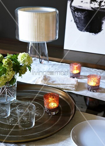 Tray of glasses and lit tealights in front of modern table lamp on table with white runner