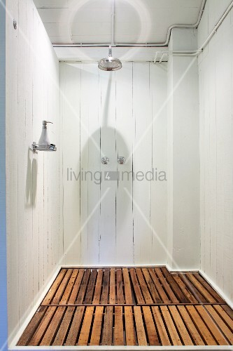 Simple Shower Area With White Wooden Walls And Wooden Slats On Floor
