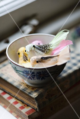 Pastel coloured decorative birds in a bowl on a stack of books