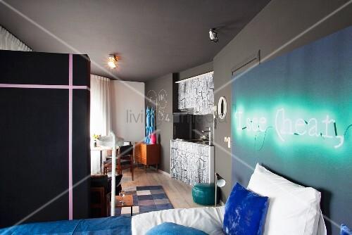 Bett an wand mit montierter leuchtschrift in offenem schlafbereich und blick auf kochnische - Leuchtschrift wand ...