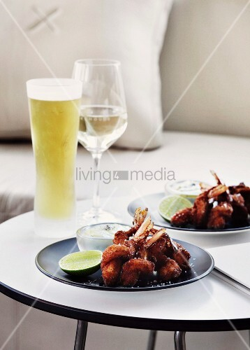 Cool drinks and snacks for two arranged on plates on round side table