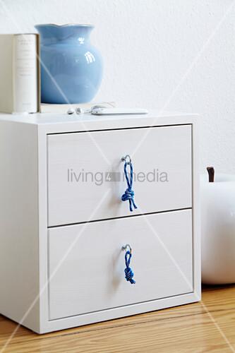 weisser nachttisch mit selbst gemachten m belkn pfen aus seil bild kaufen living4media. Black Bedroom Furniture Sets. Home Design Ideas