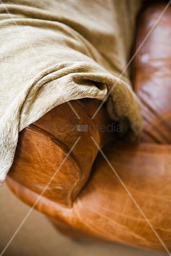 Detail of leather couch arm with throw blanket.